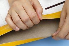 As mãos da mulher abrem o pacote amarelo Foto de Stock