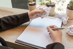 As mãos da mulher amarrotam folhas do resumo na mesa com pena, MI Foto de Stock