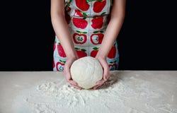 As mãos da mulher amassam a massa com farinha branca na mesa de cozinha em um fundo escuro Fotos de Stock