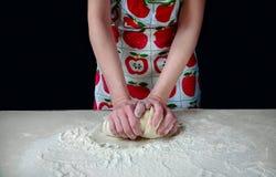 As mãos da mulher amassam a massa com farinha branca na mesa de cozinha em um fundo escuro Fotografia de Stock Royalty Free