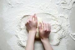 As mãos da mulher amassam a massa com farinha na aba branca da cozinha Fotografia de Stock Royalty Free