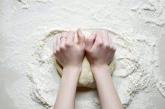 As mãos da mulher amassam a massa com farinha na aba branca da cozinha Imagens de Stock