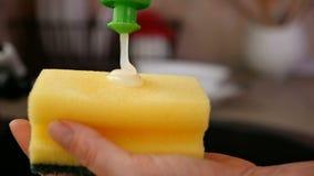 As mãos da mulher aplicam a lavagem acima do líquido na esponja - close-up filme