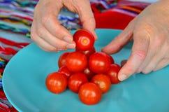 As mãos da mulher arranjam tomates de cereja em um plat Fotos de Stock Royalty Free