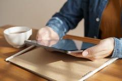 As mãos da mulher asiática estão usando a tabuleta na tabela de madeira foto de stock royalty free