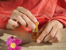 As mãos da mulher bonita que guardam um tubo de ensaio pequeno do óleo scented Attar árabe imagens de stock