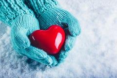 As mãos da mulher cerceta clara em mitenes feitos malha estão guardando um coração vermelho lustroso bonito em um fundo da neve C Foto de Stock Royalty Free