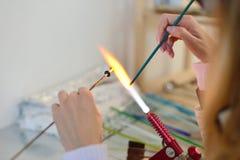 As mãos da mulher com as ferramentas para o derretimento de vidro, lampwork, fogo Foto de Stock Royalty Free