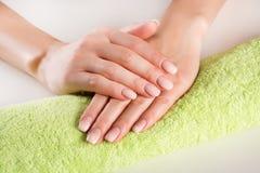 As mãos da mulher com francês do ombre pregam o tratamento de mãos na toalha verde fotos de stock