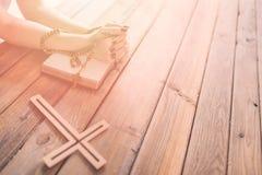 As mãos da mulher com rosário e a Bíblia Sagrada de madeira imagens de stock