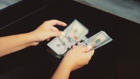 As mãos da mulher contam o salário um o bloco dos dólares no fundo preto video estoque
