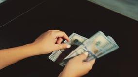 As mãos da mulher contam um bloco dos dólares no fundo preto video estoque
