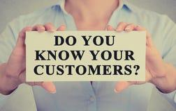 As mãos da mulher de negócios que guardam o sinal com mensagem você conhece seus clientes fotos de stock royalty free
