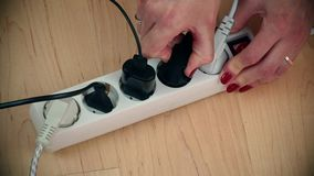 As mãos da mulher desligam o interruptor da extensão da eletricidade e desconectam fios filme