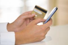 As mãos da mulher do close-up que guardaram um cartão de crédito e que usam o phon da pilha imagem de stock royalty free
