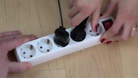 As mãos da mulher e do homem desligam o interruptor da extensão da eletricidade e desconectam fios vídeos de arquivo