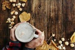 As mãos da mulher em uma camisa vermelha com cappuccino quente com pipoca, c Imagens de Stock