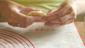 As mãos da mulher envolvem acima o enchimento no close-up da bolinha de massa 4K da fabricação de massa vídeos de arquivo