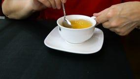 As mãos da mulher estão agitando o chá fresco quente em um copo cerâmico branco video estoque