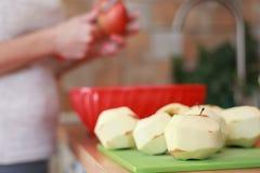 As mãos da mulher estão descascando a pele fora de maçãs vermelhas usando uma faca fotografia de stock