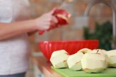 As mãos da mulher estão descascando a pele fora de maçãs vermelhas usando uma faca imagens de stock royalty free