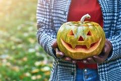As mãos da mulher nas luvas de couro mantêm uma abóbora de Dia das Bruxas exterior no parque do outono Fotografia de Stock