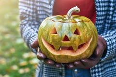 As mãos da mulher nas luvas de couro mantêm uma abóbora de Dia das Bruxas exterior no parque do outono Imagem de Stock Royalty Free