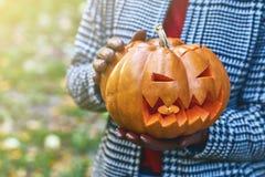 As mãos da mulher nas luvas de couro mantêm uma abóbora de Dia das Bruxas exterior no parque do outono Fotos de Stock