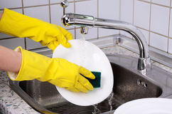 As mãos da mulher nas luvas lavam a placa 0903 horizontais Fotografia de Stock Royalty Free