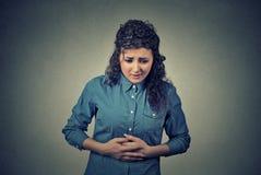 As mãos da mulher no estômago que tem dores más causam dor Fotografia de Stock Royalty Free