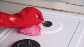 As mãos da mulher no fogão de gás sujo das lavagens de borracha vermelhas das luvas com uma escova e uma esponja vídeos de arquivo