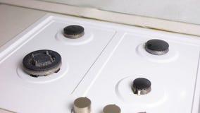 As mãos da mulher no fogão de gás sujo das lavagens de borracha vermelhas das luvas com uma escova e uma esponja filme