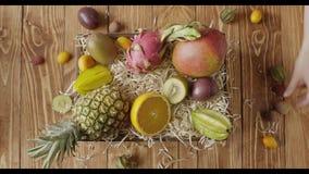As mãos da mulher puseram frutos tropicais orgânicos maduros frescos na caixa com a madeira que barbeia sobre um fundo de madeira filme
