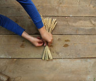 As mãos da mulher que amarram acima das orelhas do trigo com uma corda em um d de madeira Imagem de Stock Royalty Free