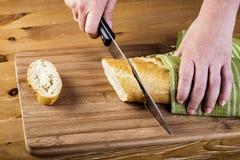 As mãos da mulher que cortam o pão na prancha de madeira Foto de Stock