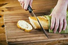 As mãos da mulher que cortam o pão na prancha de madeira Fotos de Stock