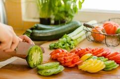 As mãos da mulher que cortam o tomate na cozinha, o outro vegetab fresco Fotografia de Stock