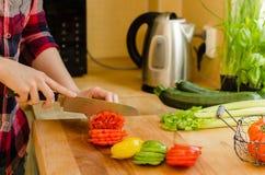As mãos da mulher que cortam o tomate na cozinha, o outro vegetab fresco Fotografia de Stock Royalty Free