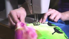As mãos da mulher que costuram na máquina de costura