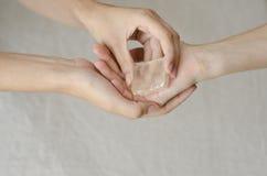 As mãos da mulher que dão um cristal de quartzo um a outro Fotos de Stock Royalty Free