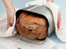 As mãos da mulher que descolam o pão do breadmaker imagem de stock