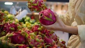As mãos da mulher que escolhem o dragão cru fresco frutificam no supermercado video estoque