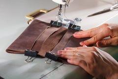 As mãos da mulher que fazem o acessório de couro Imagens de Stock Royalty Free