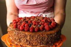 As mãos da mulher que guardam o bolo de aniversário em casa imagem de stock