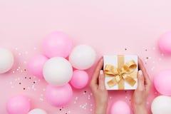 As mãos da mulher que guardam o presente ou a caixa atual na tabela pastel cor-de-rosa decoraram balões e confetes Composição lis foto de stock royalty free