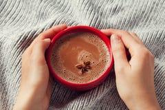 As mãos da mulher que guardam um copo do cacau quente ou do chocolate quente no fundo feito malha, bebida tradicional pelo tempo  fotografia de stock
