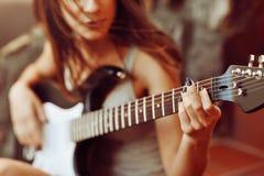 As mãos da mulher que jogam a guitarra acústica, fim acima Foto de Stock Royalty Free