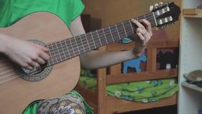 As mãos da mulher que jogam a guitarra acústica, fim acima filme