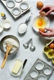 As mãos da mulher que racham um ovo sobre uma bacia ao cozer Foto de Stock Royalty Free