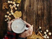 As mãos da mulher da vista superior na camisa vermelha com cappuccino com pipoca Imagem de Stock Royalty Free